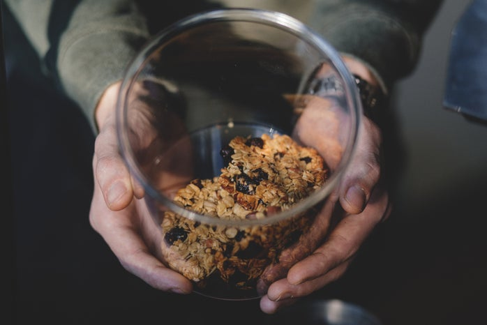 person holding a clear jar of granola