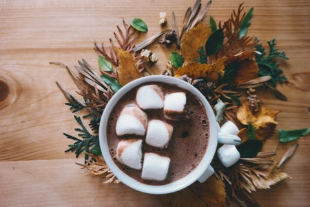 Hot Chocolate in Mug on a wooden table surrounded by leaves