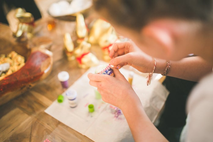Close up of girl hands coloring eggs for easter