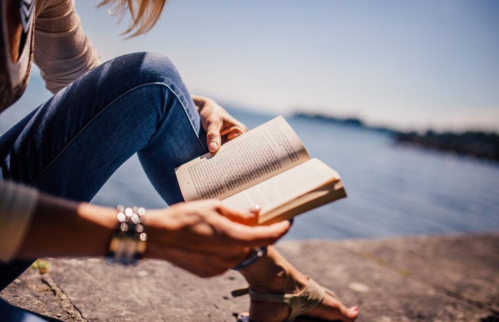 Woman Wearing Blue Denim Jeans Holding Book Sitting on Gray Concrete at Daytime