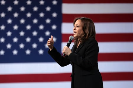 Kamala Harris speaking at an event in front of an American flag