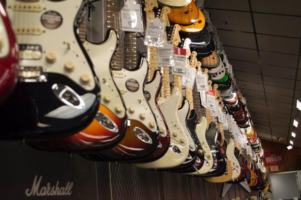 Electric Guitar Hanging Near Wall