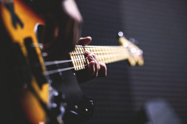 Person Playing Sun Burst Electric Bass Guitar in Bokeh Photography