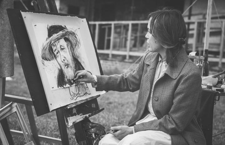 Woman Drawing a Man With Hat