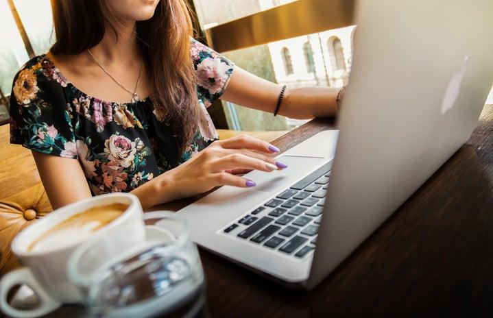 Woman Wearings Coop Neck Floral Top Using Her Apple Brand Macbook