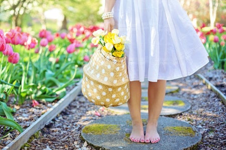 woman staning barefoot in a flower garden holding a basket of yellow flowers