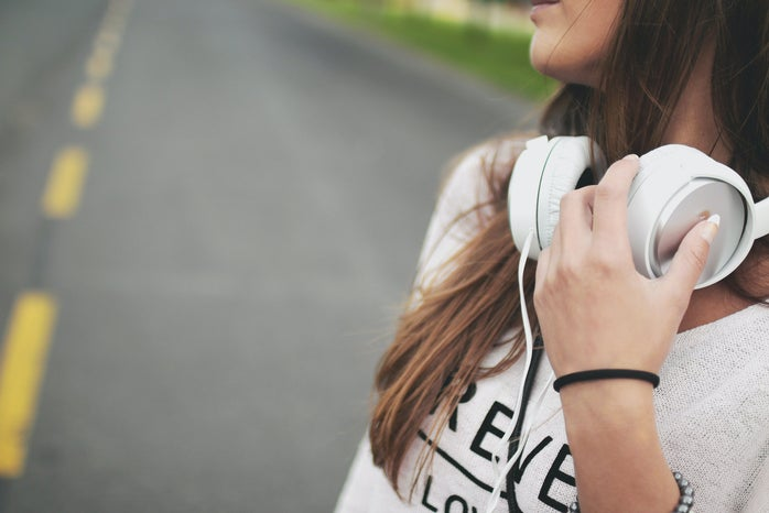 close-up of woman holding white headphones around her neck