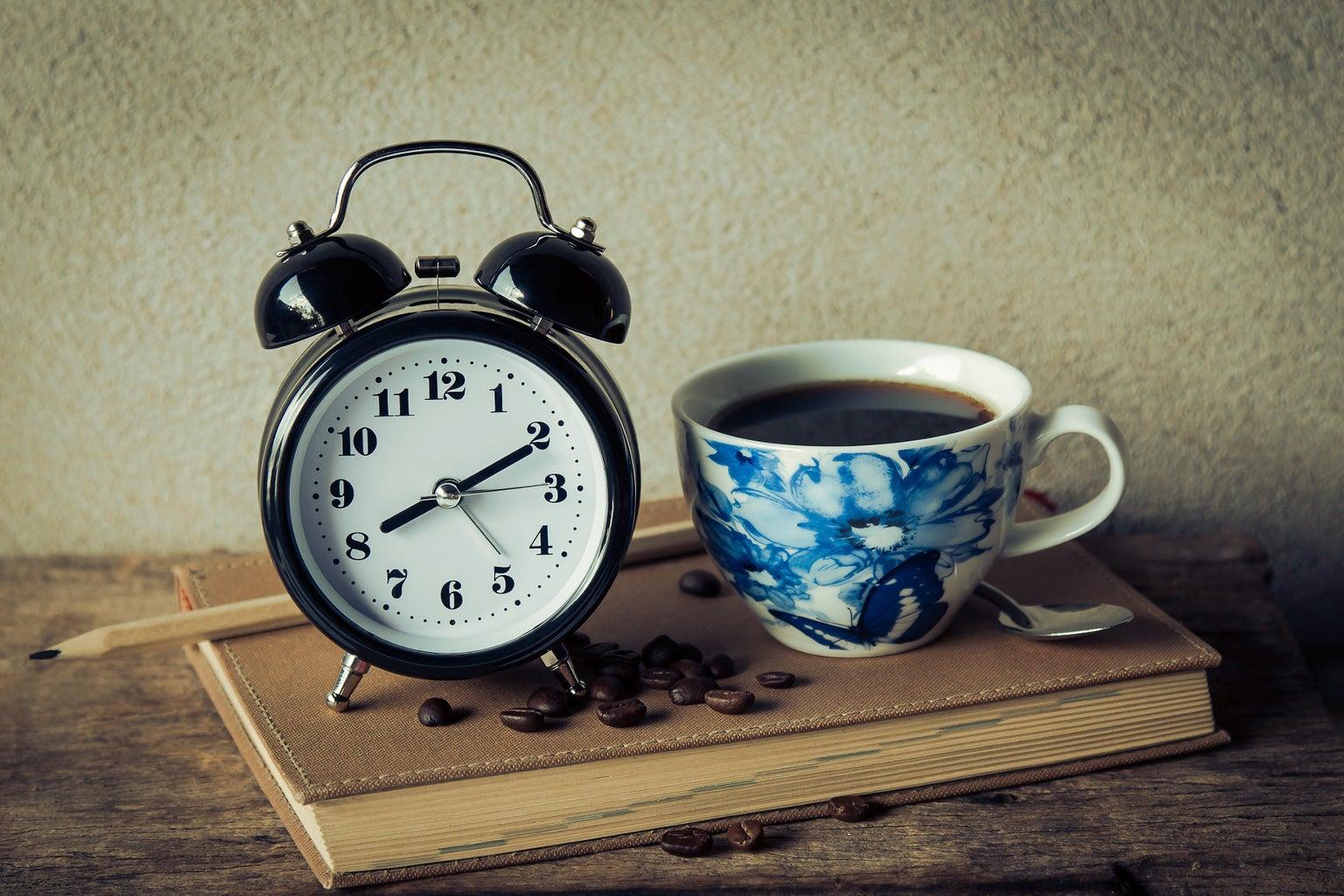 coffee in a blue pattern mug next to an analog alarm clock