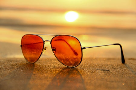 close-up of orange aviator sunglasses on sand at beach