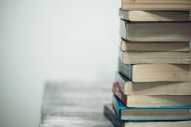 close-up of a stack of books on a grey wood table