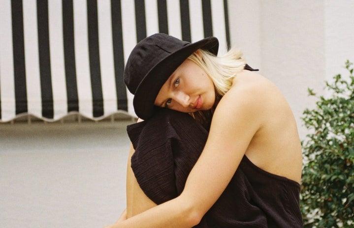 woman in a black dress wearing a bucket hat