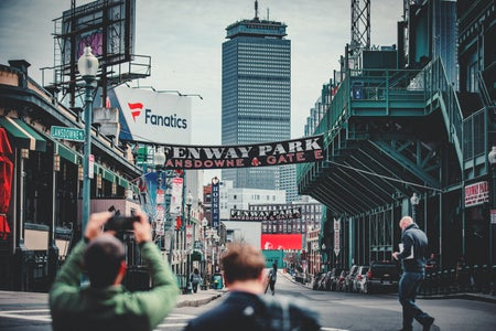 woman taking photo using DSLR camera of Landsdowne Street near Fenway Park