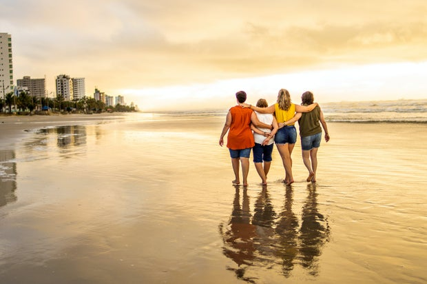 4 women walking arm-in-arm on beach during sunset