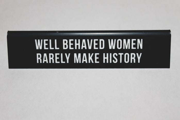 """black placard stating on \""""WELL BEHAVED WOMEN RARELY MAKE HISTORY\"""" on white table"""