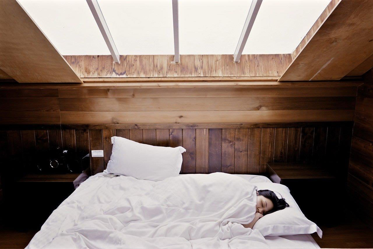 person sleeping in white bed