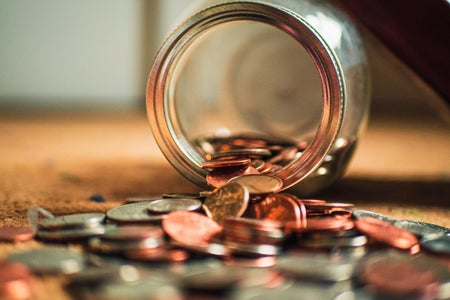 Pile of US coins spilling out of glass jar