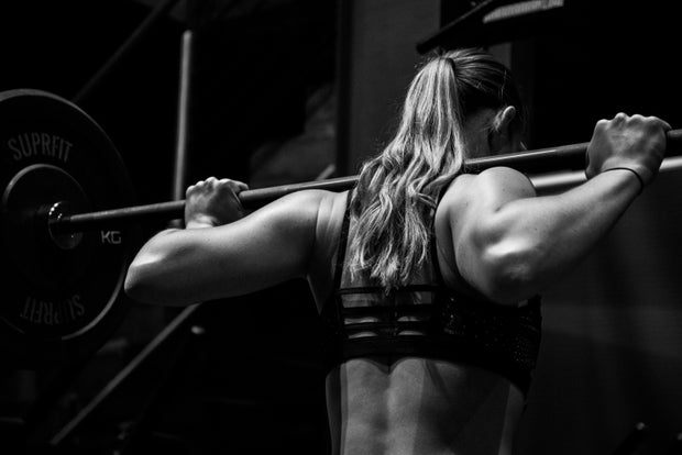 black and white photo woman lifting barbell