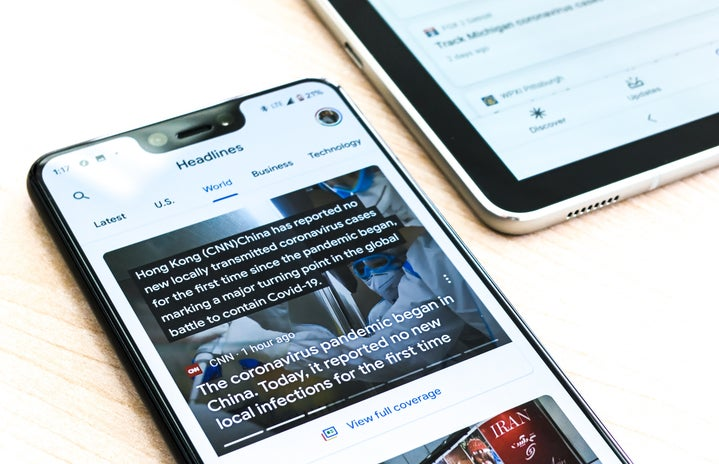 silver iphone 6 on brown wooden table with news feed on screen