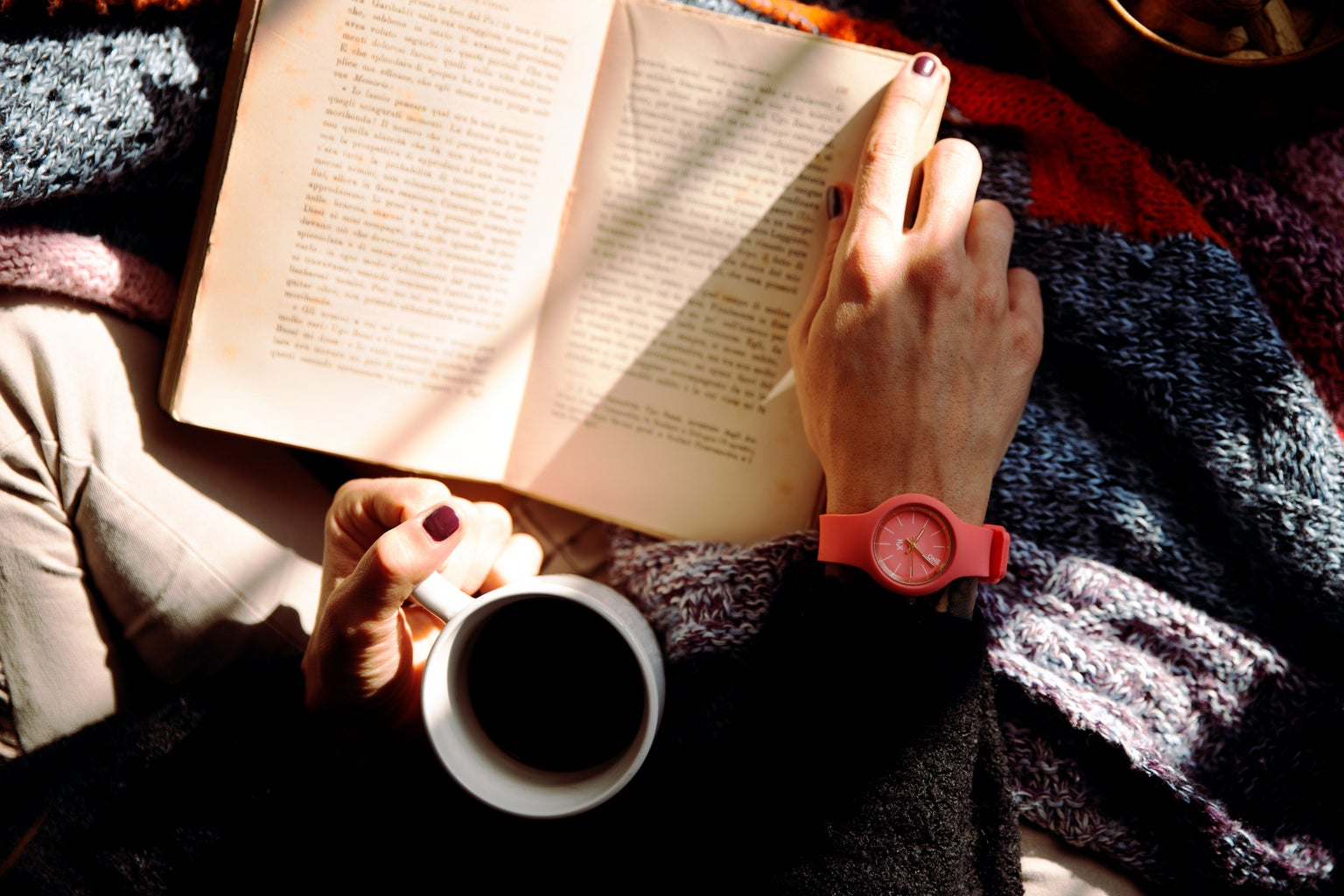 Girl holding cup of coffee and book