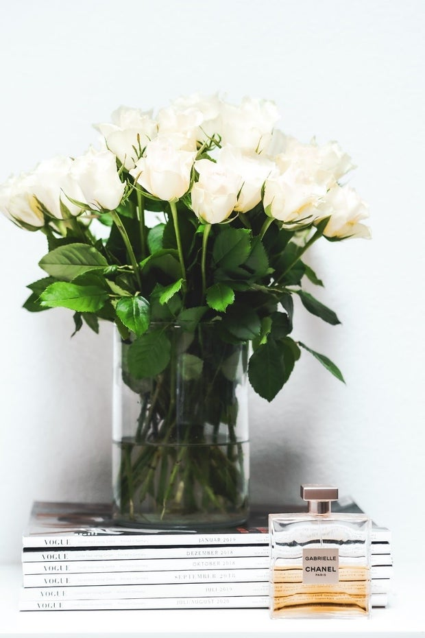 white tabletop with vase of white roses and two books, a bottle of Chanel perfume
