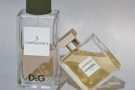 product shot of two designer perfumes, one leaning against the other