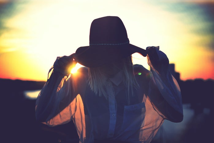 silhouette of woman holding her hat