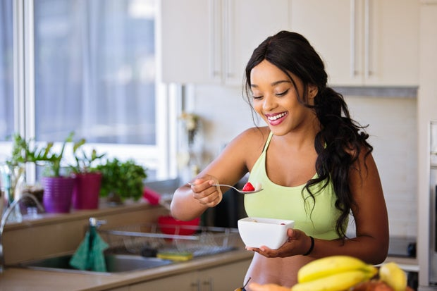 woman eating fresh fruit in a sports bra