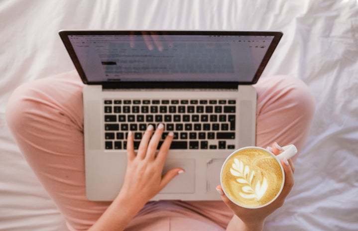 drinking a latte while on laptop on bed