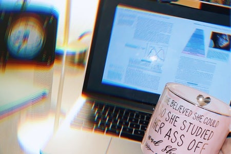 Student holding coffee cup while studying at desk