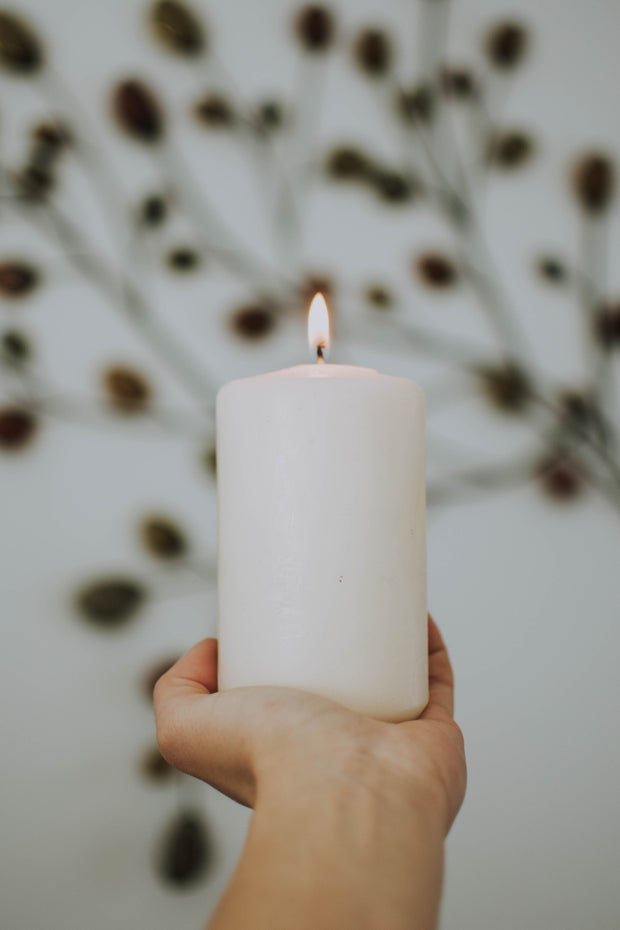 Hand holding lit white pillar candle