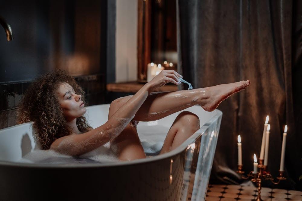 Woman shaving her legs in the bathtub