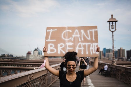 "woman holding a sign that says ""I can't breathe"""