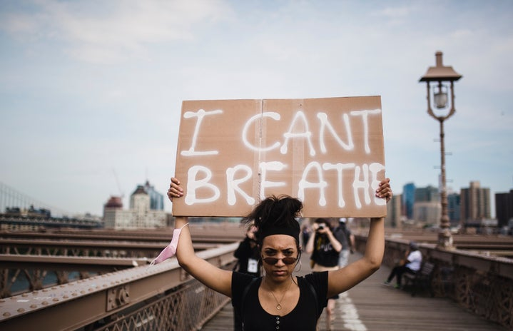 """woman holding a sign that says """"I can't breathe"""""""