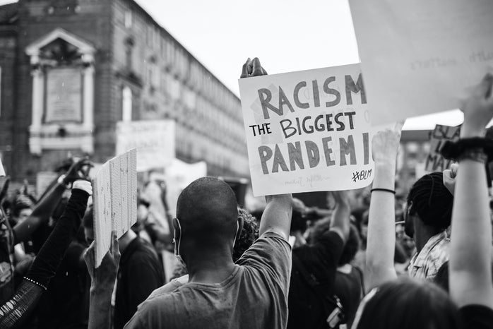 """person holding a sign that says \""""racism is the biggest pandemic\"""""""