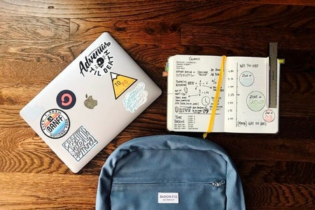 Flat lay of bookbag, laptop and notebook