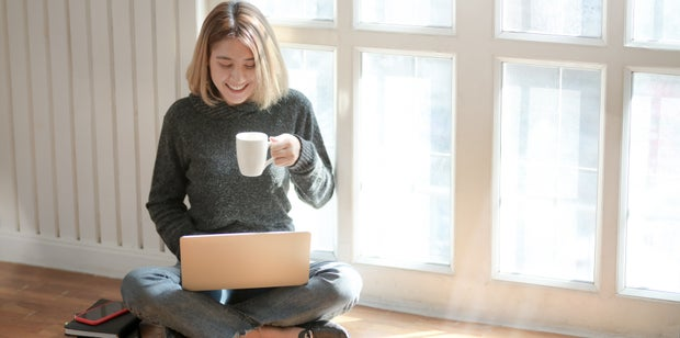 Woman sitting at computer drinking coffee