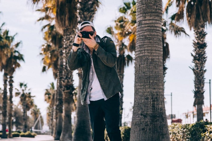 guy taking picture, palm trees in back