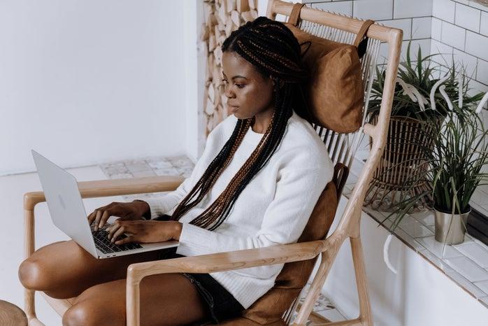 Woman sitting in chair on laptop