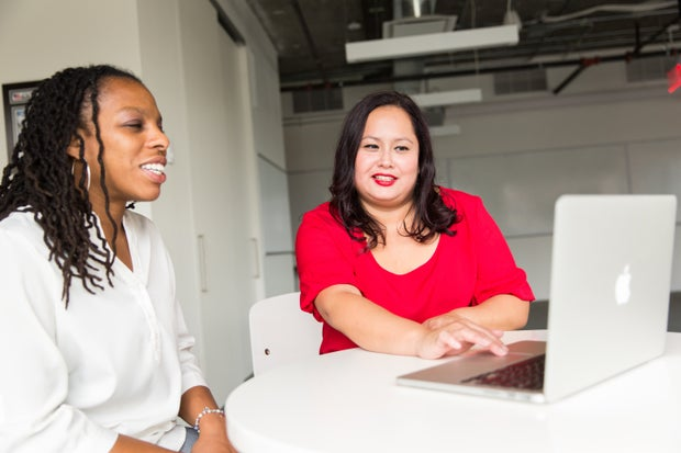 Two women of color sitting at a table together. One is wearing a bright red shirt and the other wearing a white  shirt. There is a macbook in front of them on a table.