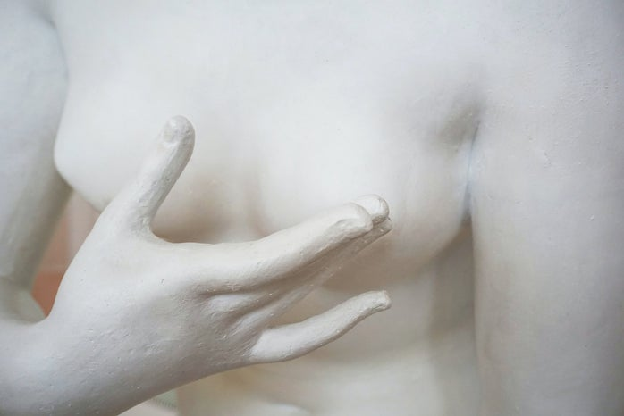 A marble statue of a person touching their left breast.