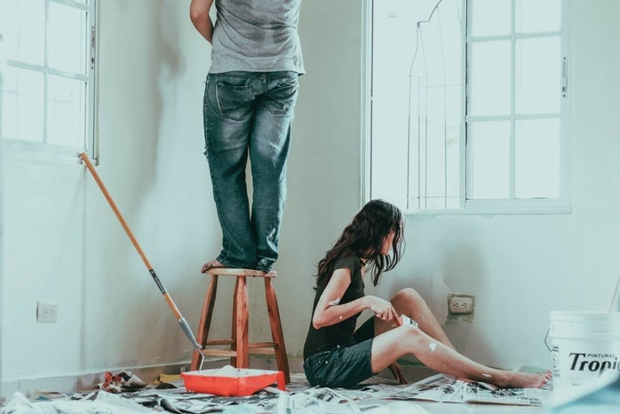 man standing on stool and woman sitting on floor while painting walls in white
