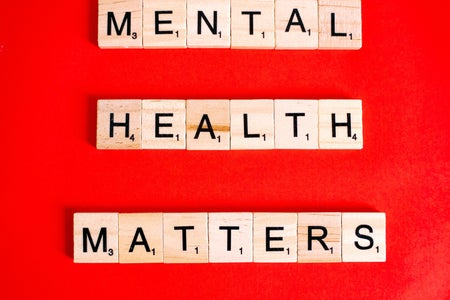 "block letters spelling out ""mental health matters"" on a red background"