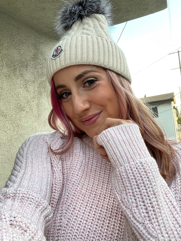 Selfie of a girl in a sweater and hat with a pom pom