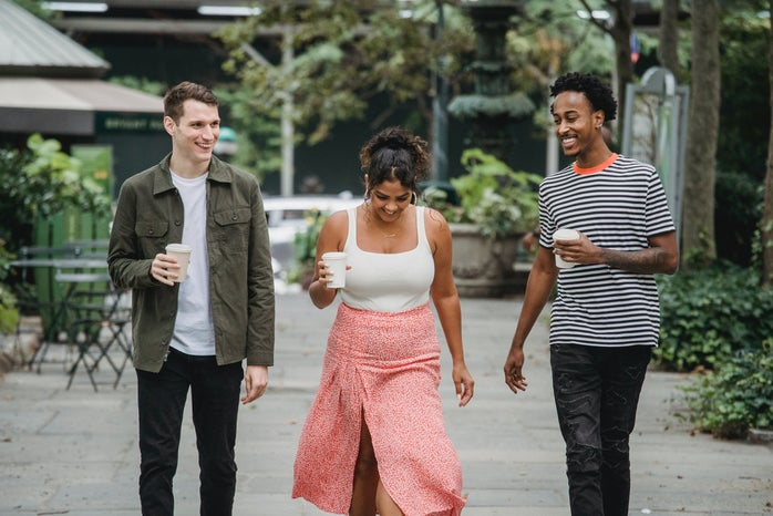 young friends walking in park and smiling with coffee to go