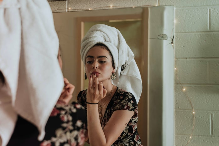 Woman putting lipstick on, a towel on her head.
