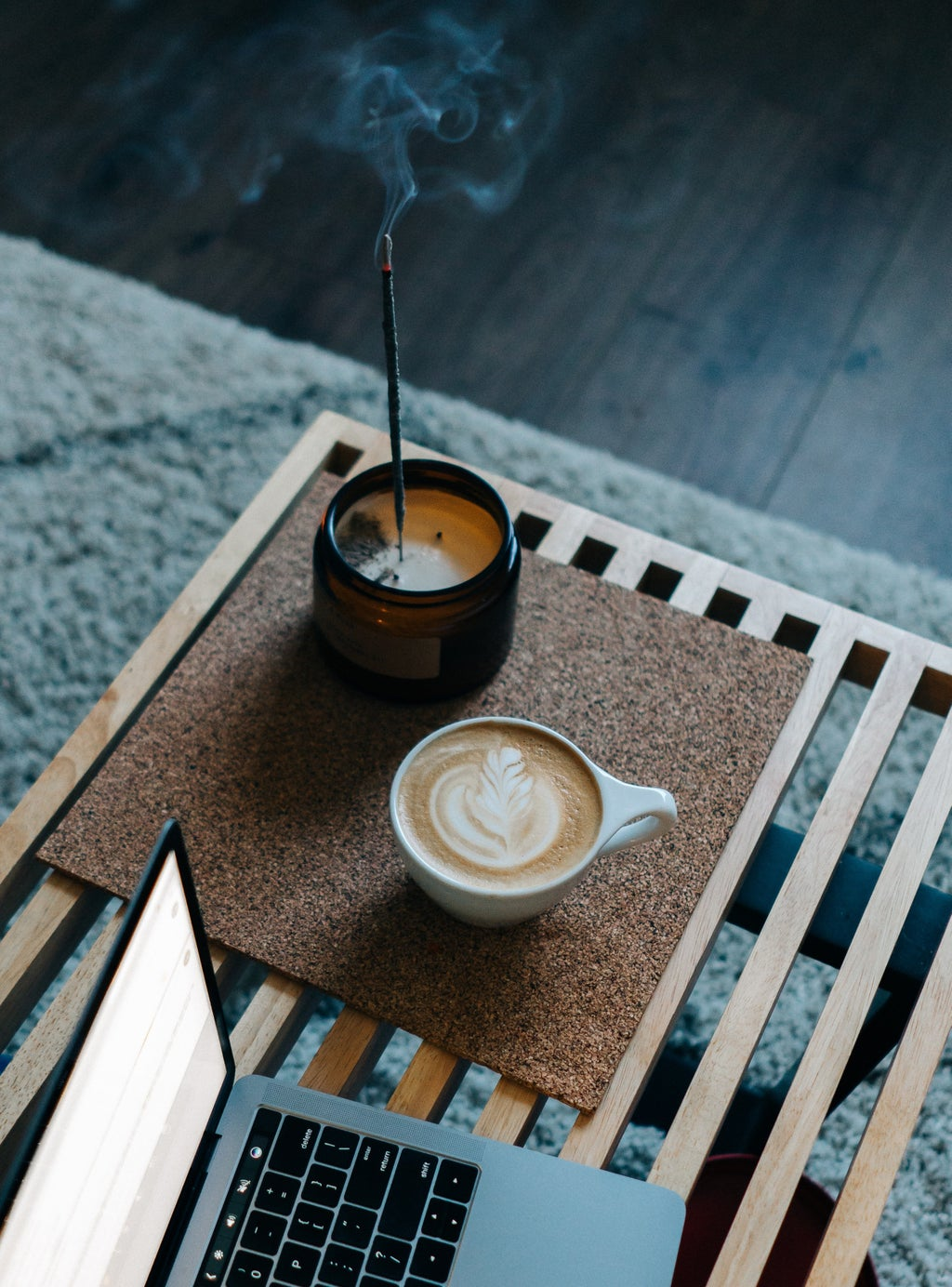 Cappuccino and candle next to laptop