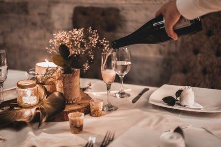 Waiter pouring champagne into glassware for celebration