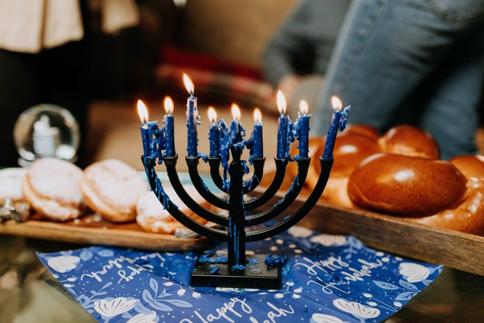 lit menorah surrounded by challah and jelly donuts for hanukkah