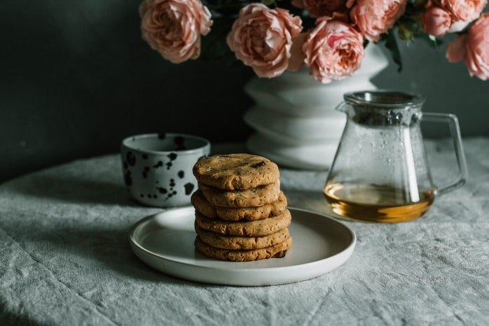 cookies stacked on a plate with table cloth and flowers in background