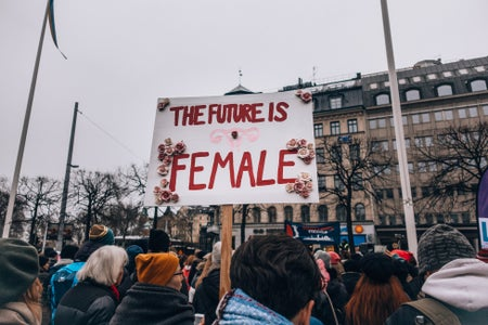 "Protester holds ""The future is female"" sign in Sweden"